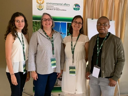 A photograph of four people who are part of the Collaboration for Environmental Evidence Johannesburg team standing in front of a sign for the 4th annual Biodiversity and Evidence Indaba, hosted by the South African Department for Environment, Forestry, and Fisheries.